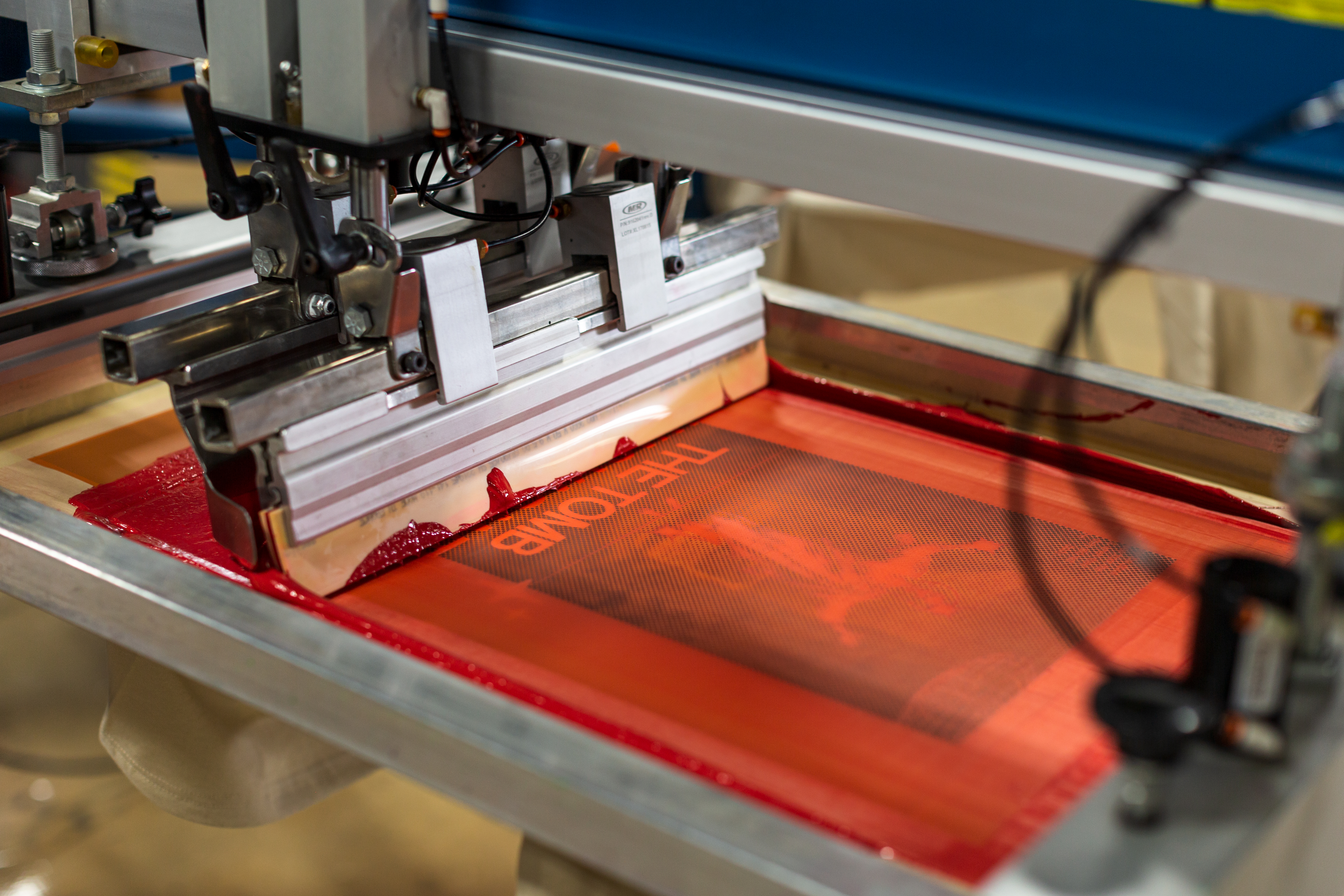 a screen print with the color orange being applied to a shirt